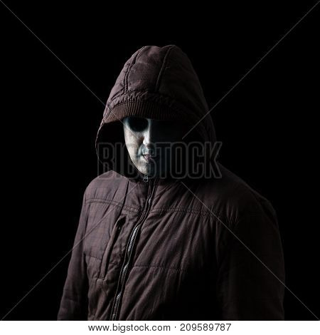 Scary and creepy male monster with gouged eyes looking like a skull and pale white and green skin  standing in the darkness and hiding in the shadows. Low key, black background. Concept for Halloween
