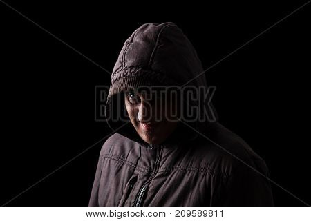 Mature man with a scary and creepy smile hiding in the shadows, with the face partly hidden with the hood, and standing in the darkness. Black background. Concept for stalker, fear, danger, crime,