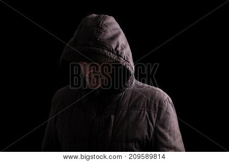 Scary and creepy man hiding in the shadows, with the face and identity hidden with the hood, and standing in the darkness. Low key, black background. Concept for fear, mystery, danger, crime, stalker