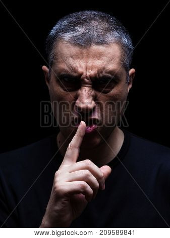 Furious mature man with an aggressive look making the silence sign in a violent and threatening way. Low key, black background. Concept for threat, anger, rage, violence, danger, menace, fury.