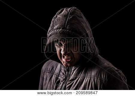 Very angry and aggressive man hiding in the shadows, with the face partly hidden with the hood, and standing in the darkness. Low key, black background. Concept for anger, rage, violence, danger