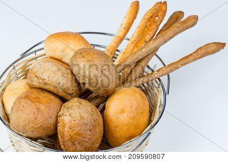 Homemade bread in wicker basket on white background