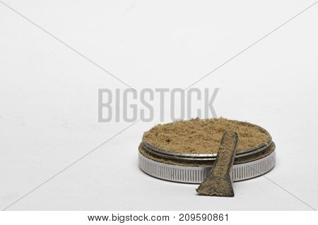 Off center Isolated cannabis kief in a white background