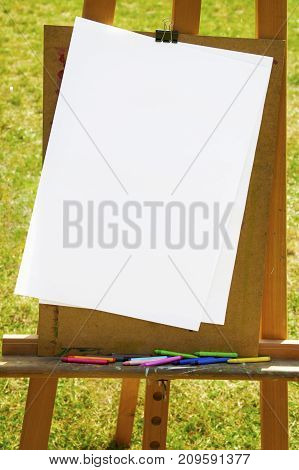 Wooden easel with white paper and crayons on green grass sunny day outside.