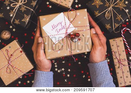 Man hands holding christmas holiday gift box with postcard merry xmas on decorated festive table with sparkle stars candy cane walnut on wooden background. Packaging gift wrap and ribbons twine. Winter time new year