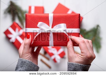 Close up of young woman hands holding red Christmas present above white wooden background. Christmas background with red gift boxes. Flat lay top view