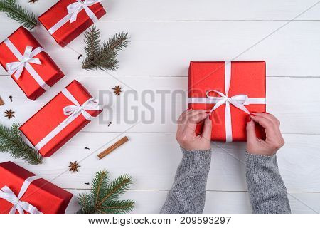 Woman holding red Christmas present laying on white wooden background. Christmas background with red gift boxes fir tree branches pine cones cinnamon sticks and stars anise. Flat lay top view