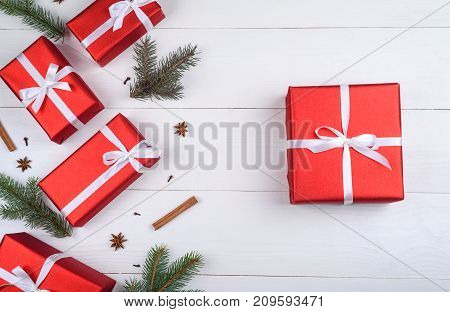 Christmas background with red gift boxes fir tree branches pine cones cinnamon sticks and stars anise on white wooden background free space. Holiday greeting card copy space. Flat lay top view