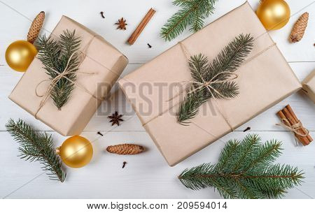 Christmas background with gift boxes wrapped in kraft paper fir tree branches golden glass balls pine cones cinnamon sticks and stars anise on white wooden background. Flat lay top view