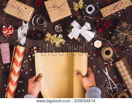 Man hand unfolding roll of wrapping kraft paper for packing christmas gift box. Process of package new year gift box. Christmas packaging wrapping paper ribbon twine bow and thread scissors balls on wooden background. Winter time new year