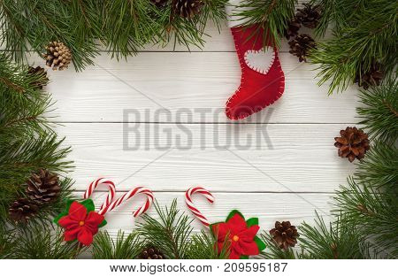Template for Christmas card with fir tree border and copy space. Wooden table and natural pine branches.