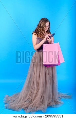 Beautiful young woman in dress holding shopping bags and using mobile smart phone over blue background in black friday holiday free space. Beauty fashion seasonal sale concept copy space