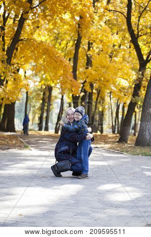 Young Mother and little son in autumn park. Concept of friendly family.