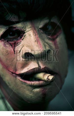 closeup of a scary disfigured man with a bloody finger in his mouth