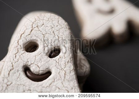 closeup of some cookies in the shape of a ghost, on a dark gray surface