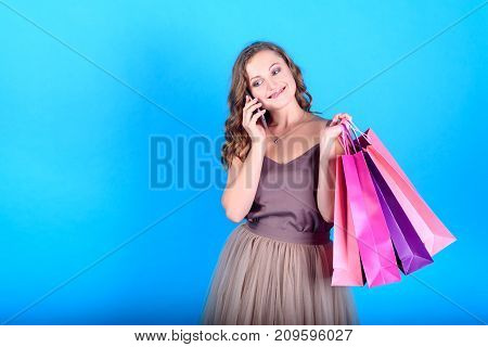 Happy young smiling woman in dress holding shopping bags and talking on mobile smart phone over blue background in black friday holiday free space. Beauty fashion seasonal sale concept copy space
