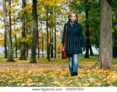Happy young woman with autumn leaves in her hand walking in autumn park