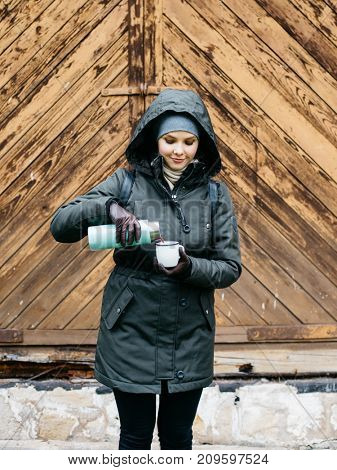 Young woman pouring a hot herbal tea in mug from thermos outdoors