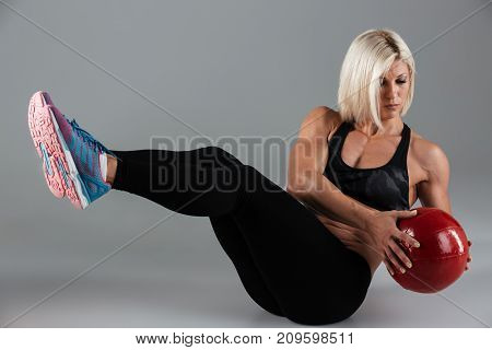 Portrait of a focused muscular adult sportswoman doing abs exercises with a heavy ball isolated over gray background