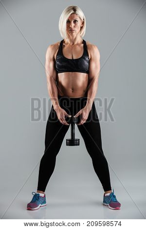 Full length portrait of a serious muscular adult sportswoman holding heavy dumbbell while standing isolated over gray background