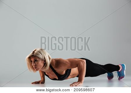 Full length portrait of a strong muscular adult sportswoman doing push-ups isolated over gray background