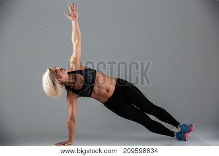 Full length portrait of a strong muscular adult woman doing plank exercise with on hand isolated over gray background