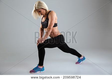 Full length portrait of a strong adult female athlete doing stretching exercises isolated over gray background