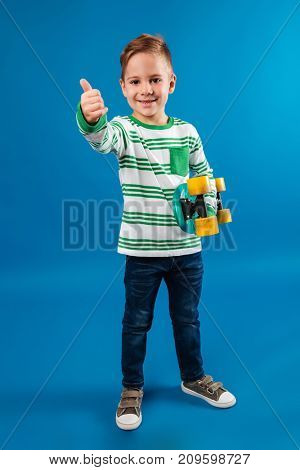 Full length image of smiling young boy holding skateboard and showing thumb up at camera over blue background