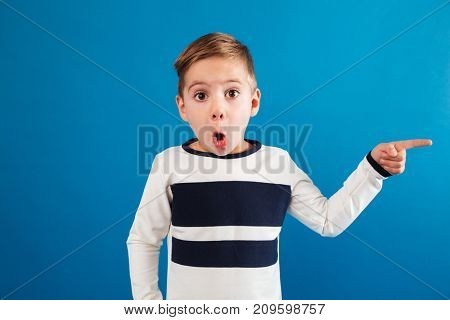 Shocked young boy in sweater pointing away and looking at the camera over blue background
