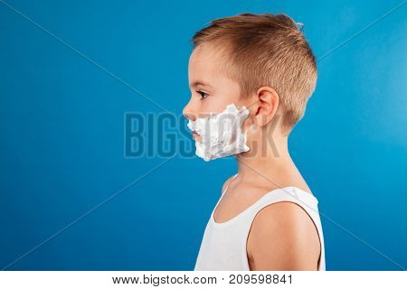 Profile of young serious boy in shaving foam like man posing over blue background