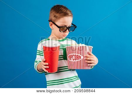 Calm young boy in eyeglasses preparing to watch the film while holding soda and looking at popcorn over blue background