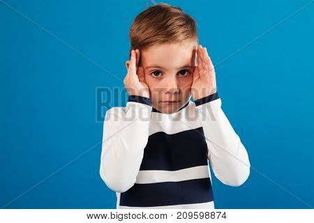 Young boy in sweater holding his hands near the eyes and looking at the camera over blue background