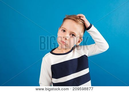 Pensive young boy in sweater touching his head and looking away over blue background
