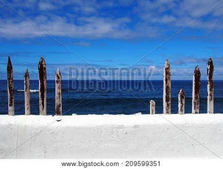 white painted wall with blue sea to the horizon with summer sky and clouds with old wooden fence posts