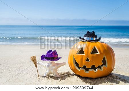 Ocean Happy Halloween background with pumpkin and starfish on the beach