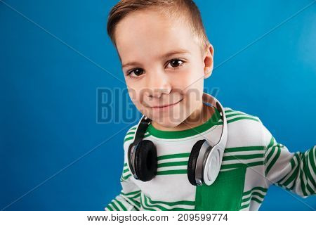 Close up image of smiling young boy posing with headphone and looking at the camera over blue background