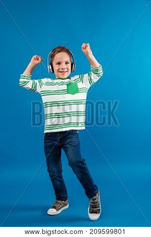 Full length image of carefree young boy listening music and dancing over blue background