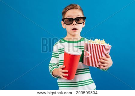 Surprised young boy in eyeglasses preparing to watch the film while holding soda and popcorn over blue background