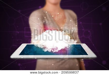 Casual young woman holding tablet with cloud concept and purple background