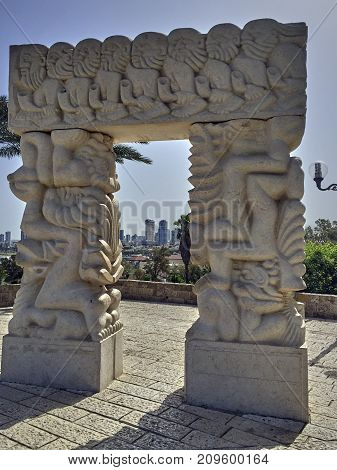 View by a white sculpture gate of faith in Jaffa. In the background is the skyline of Tel Aviv to see
