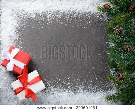 Two christmas gift boxes with ribbons on a dark stone slate table snowflakes frame copyspace fir branches with cones top view