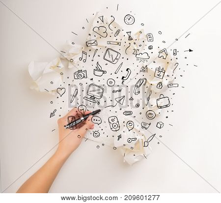Female hand next to a few crumpled paper balls drawing mixed media icons