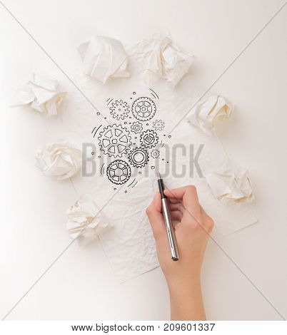 Female hand next to a few crumpled paper balls drawing rotating gears