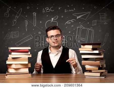 A passionate young teacher sitting at school desk with pile of books in front of blackboard drawn full of back to school items concept.