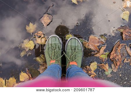 Selfi Legs clouse up in green sneakers standing in a puddle where the fallen leaves float