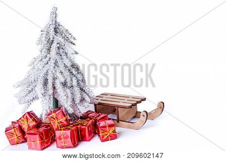 Christmas tree in snow with red xmas gift under the Christmas tree. Christmas and New Year concept. Christmas greeting card.