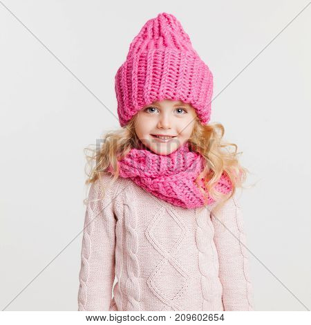 Winter clothes. Portrait of little curly girl in knitted pink winter hat and scarf isolated on white. Big blue eyes
