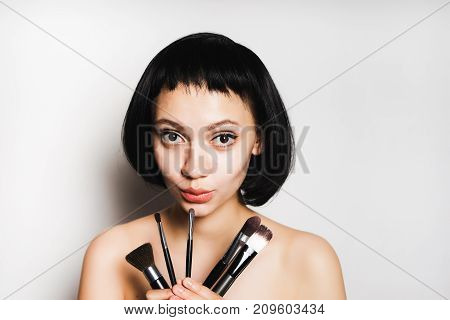 girl with black hair is holding a set of brushes