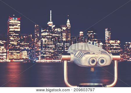 Vintage toned binoculars with New York City skyline at night USA.