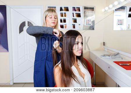 Positive and professional barber women styling hair with equipment of a beautiful female client on a blurred barbershop background. Copy space.